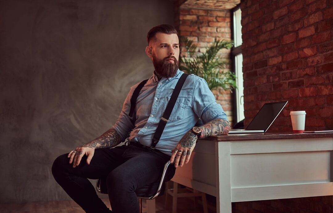 Handsome tattooed hipster in a shirt and suspenders sitting at the desk with a computer, looking out the window in an office with a loft interior.
