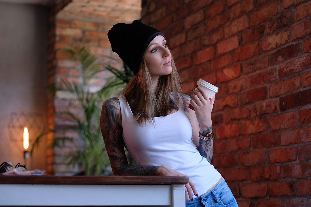 Portrait of a blonde tattoed girl dressed in white t-shirt and hat holds takeaway coffee while leaning on a table in a room with loft interior.