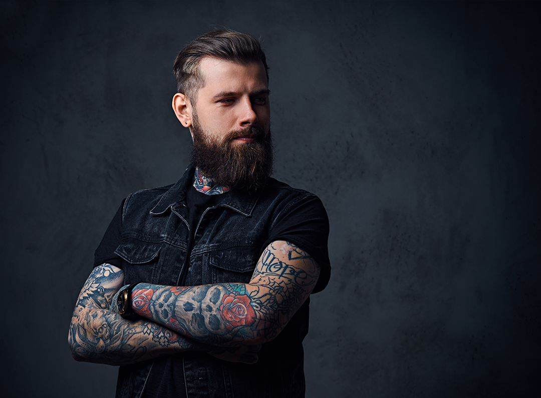Studio portrait of bearded hipster male with tattoos on his arms and neck dressed in a black shirt and waistcoat.