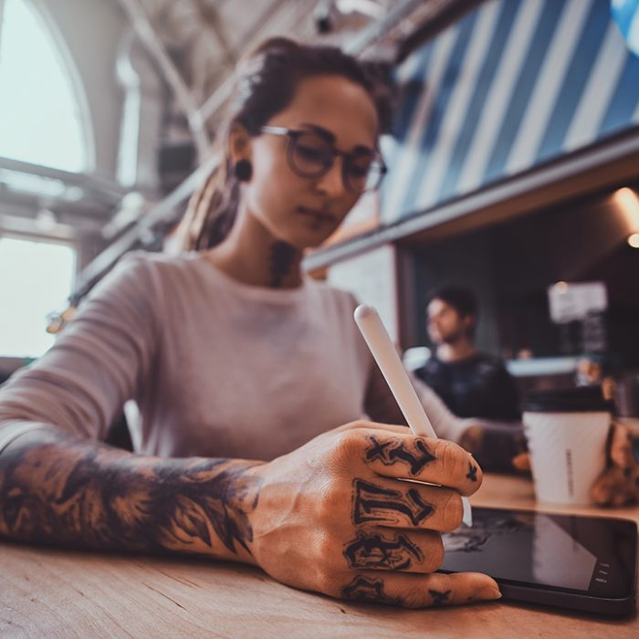Low angle photo of attractive pensive girl with dreadlocks and tattooes. Dhe is sketching while sitting at cafe.